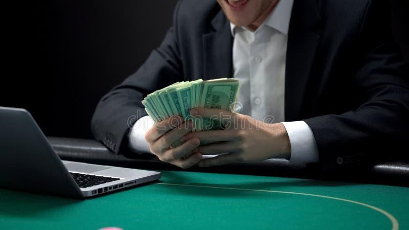 Homme enthousiaste recevant le prix du dollar, pari en ligne réussi, fortune de jeu photographie stock libre de droits