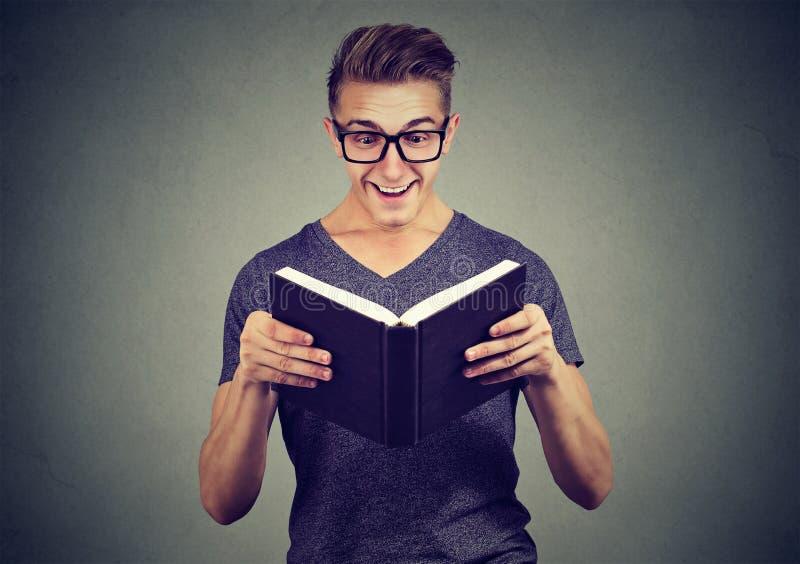 Homme enthousiaste regardant le livre photographie stock
