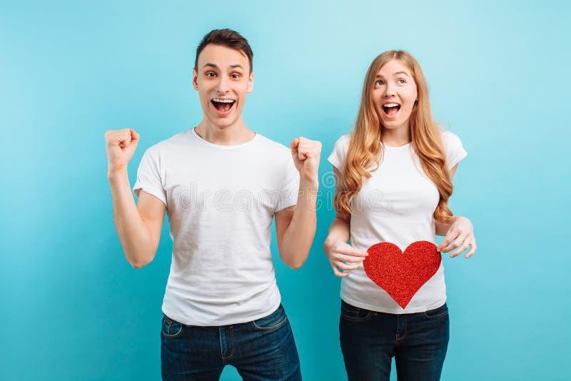 Homme enthousiaste se renseignant sur la grossesse de son épouse, une femme enceinte tenant un coeur de papier rouge contre le ve image stock