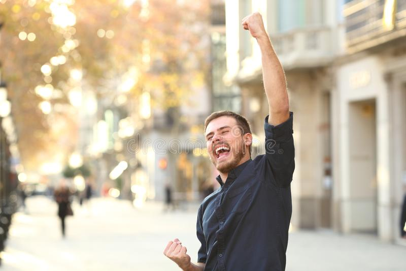 Homme enthousiaste soulevant des bras célébrant le succès photographie stock