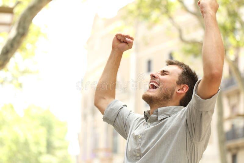 Homme enthousiaste soulevant des bras dans la rue image stock