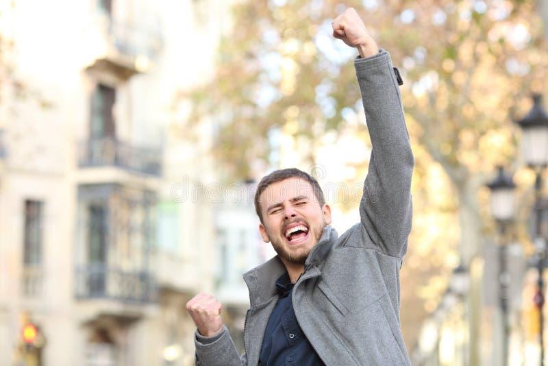 Homme enthousiaste soulevant le bras dans la rue photos stock