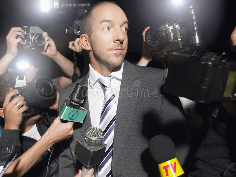 Homme entouré par des paparazzi image libre de droits