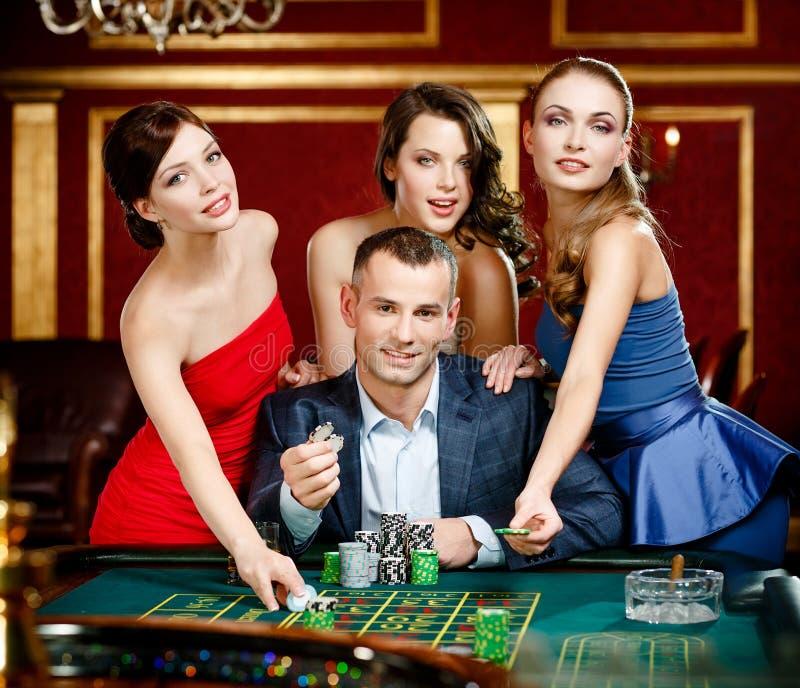 Homme entouré par la roulette de jeux de filles image stock
