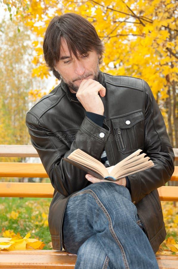 Homme entre deux âges avec un livre en stationnement image stock