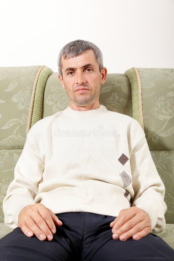 Homme entre deux âges sur le sofa photos libres de droits
