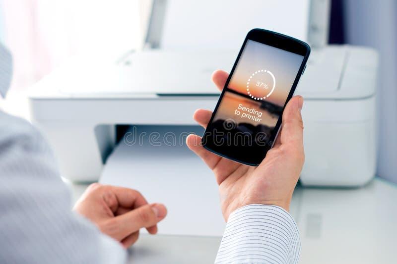 Homme envoyant une photo à l'imprimante sans fil photo stock