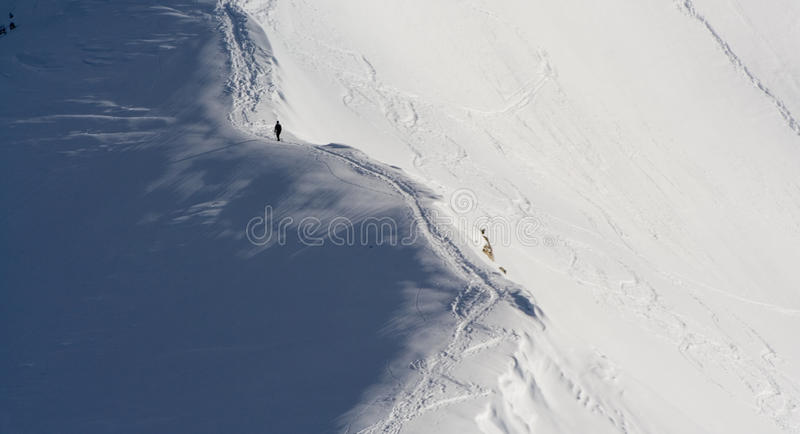 Homme escaladant la montagne neigeuse photo stock
