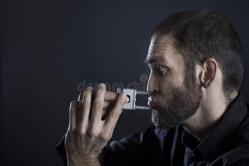 Homme essayant de déchirer le cadenas des lèvres image stock