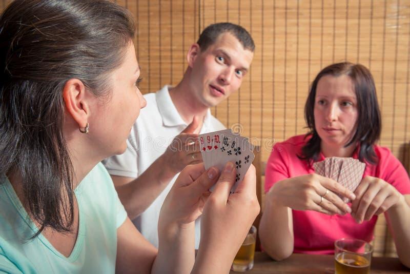 Homme et deux femmes jouant le tisonnier images stock