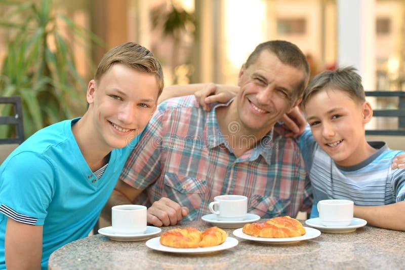 Homme et deux garçons prenant le petit déjeuner images stock