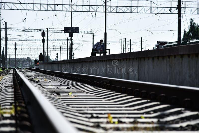 Homme et enfant attendant le train à la gare ferroviaire photos stock