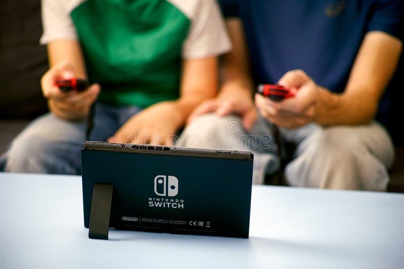 Homme et enfant jouant la console de jeu vidéo de commutateur de Nintendo images libres de droits