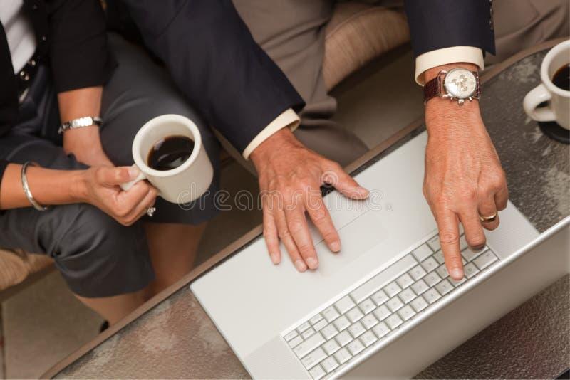 Homme et femme à l'aide de l'ordinateur portatif avec du café photographie stock libre de droits