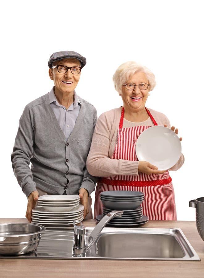 Homme et femme âgés debout avec un tas de plaques propres images stock