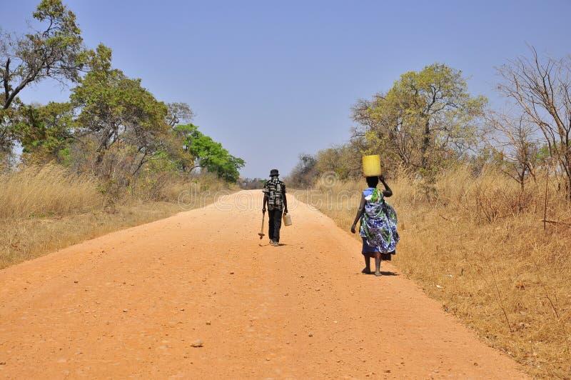 Homme et femme africains sur la route d'Africain de la poussière photo stock