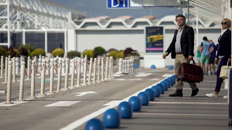 Homme et femme allant prendre le taxi de l'aéroport au centre de la ville, voyage d'affaires photos stock