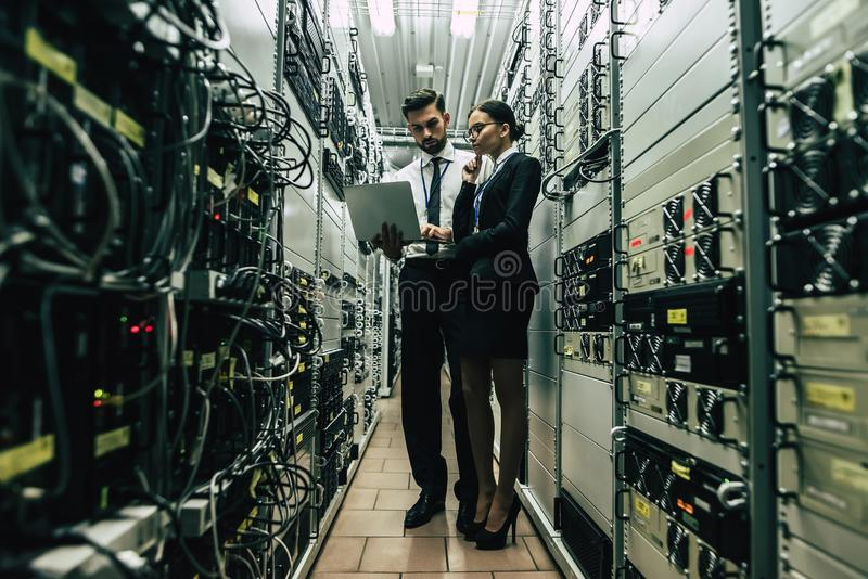 Homme et femme au centre de calculs image stock