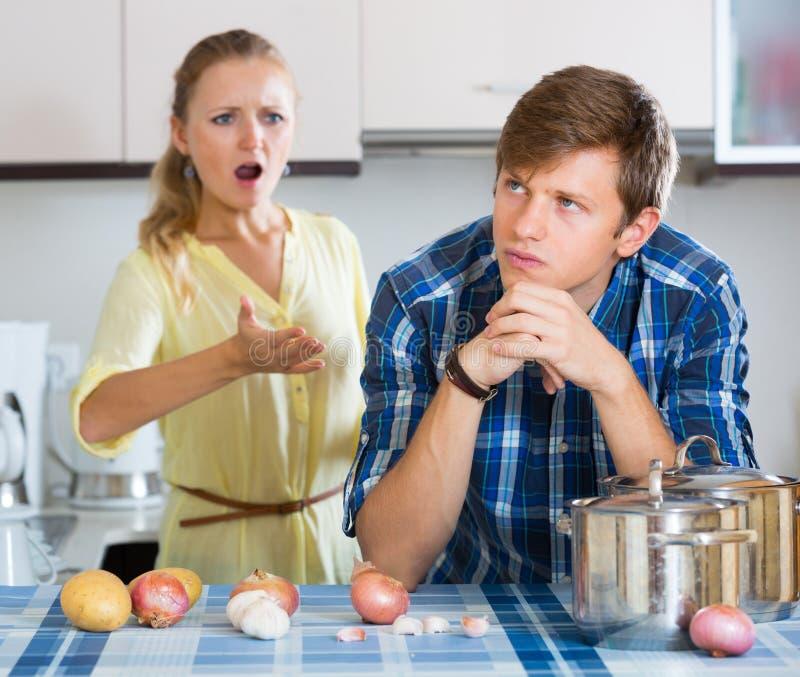 Homme et femme au foyer frustrante ayant le mauvais argument photos stock