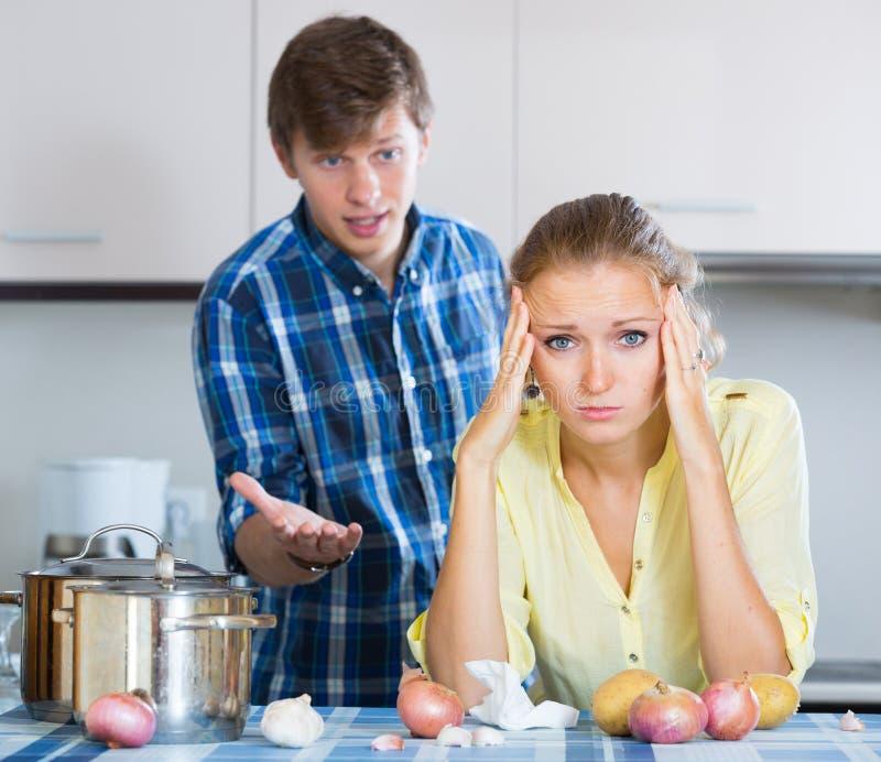 Homme et femme au foyer frustrante ayant le mauvais argument photographie stock