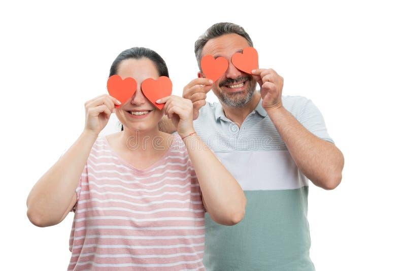 Homme et femme couvrant des yeux de coeurs photo stock
