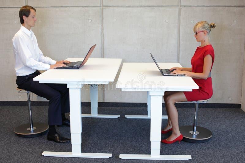 Homme et femme d'affaires dans des positions assises correctes dans le bureau photos stock