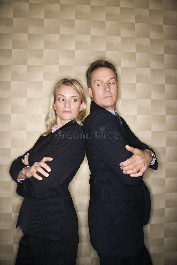 Homme et femme d'affaires de nouveau au dos image stock