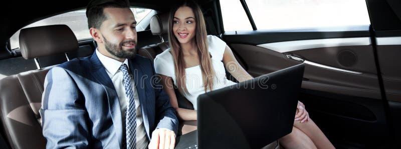 Homme et femme d'affaires travaillant ensemble dans la voiture images stock