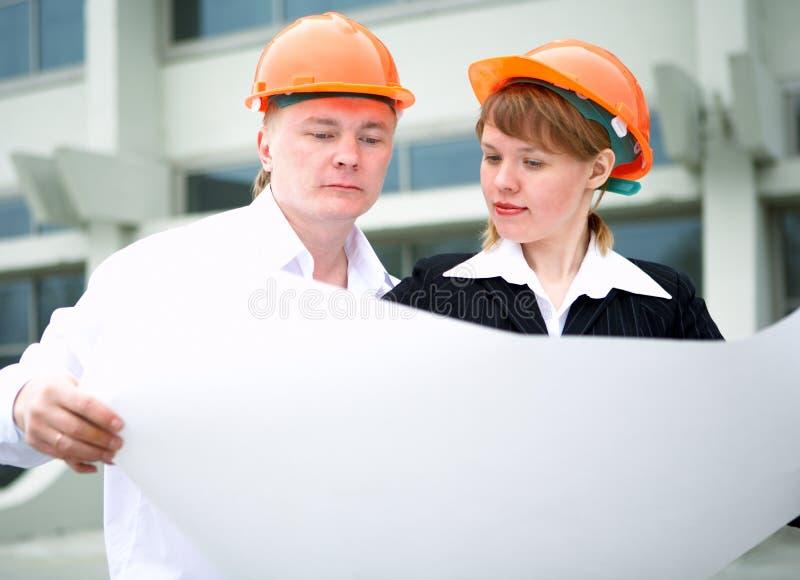 Homme et femme d'architecte dans le casque photographie stock libre de droits