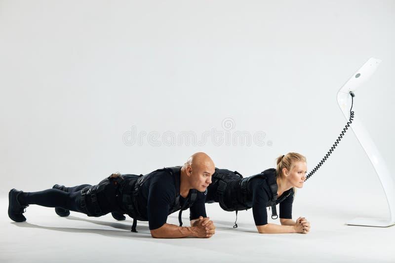 Homme et femme dans les costumes musculaires ?lectriques de stimulation faisant l'exercice de planche photographie stock libre de droits