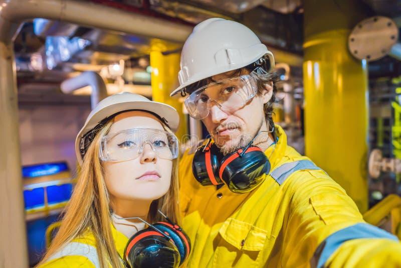 Homme et femme dans un uniforme jaune, les verres, et le casque de travail dans un milieu industriel, une plateforme pétrolière o photo stock
