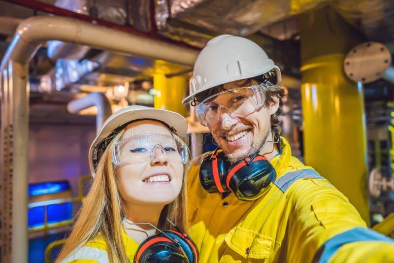 Homme et femme dans un uniforme jaune, les verres, et le casque de travail dans un milieu industriel, une plateforme p?troli?re o images stock