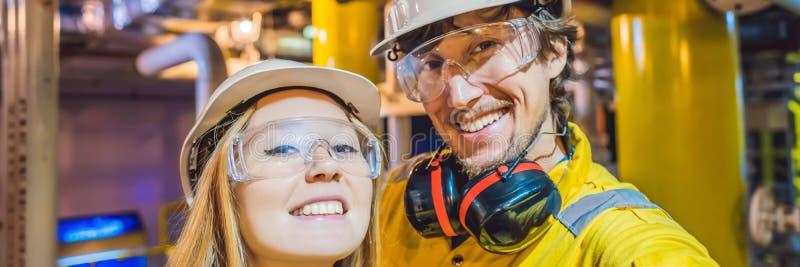 Homme et femme dans un uniforme jaune, les verres, et le casque de travail dans un milieu industriel, une plateforme p?troli?re o image libre de droits