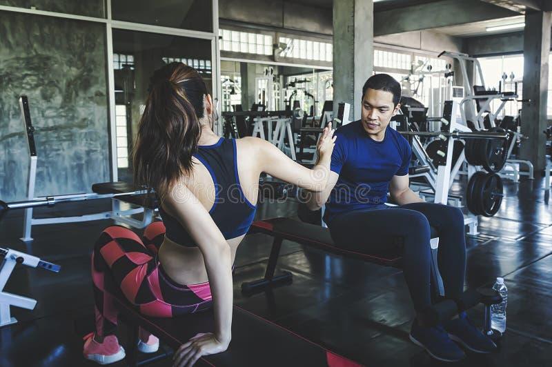 Homme et femme de forme physique se donnant de hauts cinq après le stage de formation dans le gymnase Couples convenables hauts c images stock