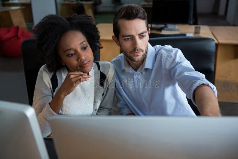 Homme et femme discutant au-dessus du PC de bureau images libres de droits