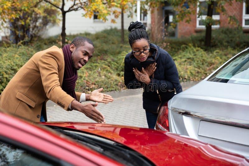 Homme et femme discutant les uns avec les autres apr?s accident de voiture photographie stock libre de droits