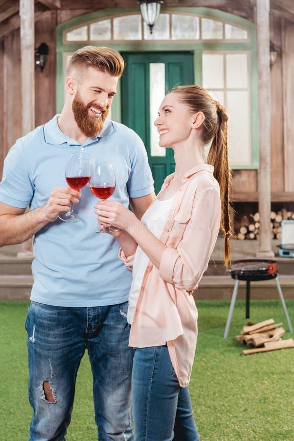 Homme et femme embrassant et tenant le vin dans des verres à vin photographie stock