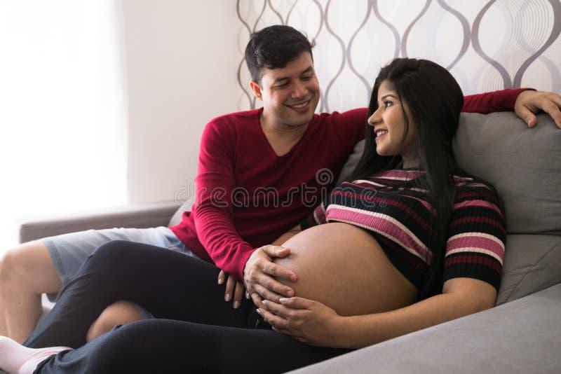 Homme et femme enceinte dans le salon photo stock