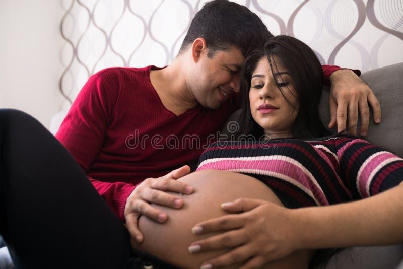 Homme et femme enceinte dans le salon images stock