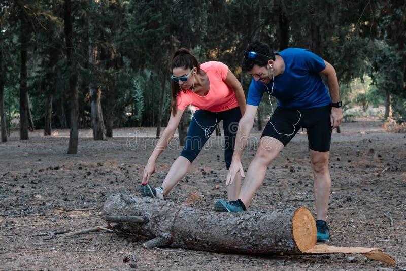 Homme et femme faisant des exercices d'étirement en plein air photos stock