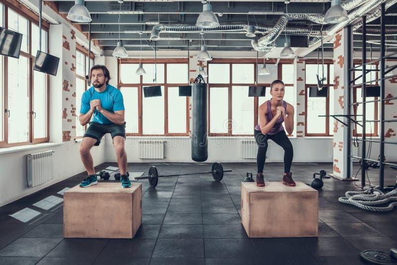 Homme et femme faisant des postures accroupies sur les blocs en bois dans le gymnase image stock