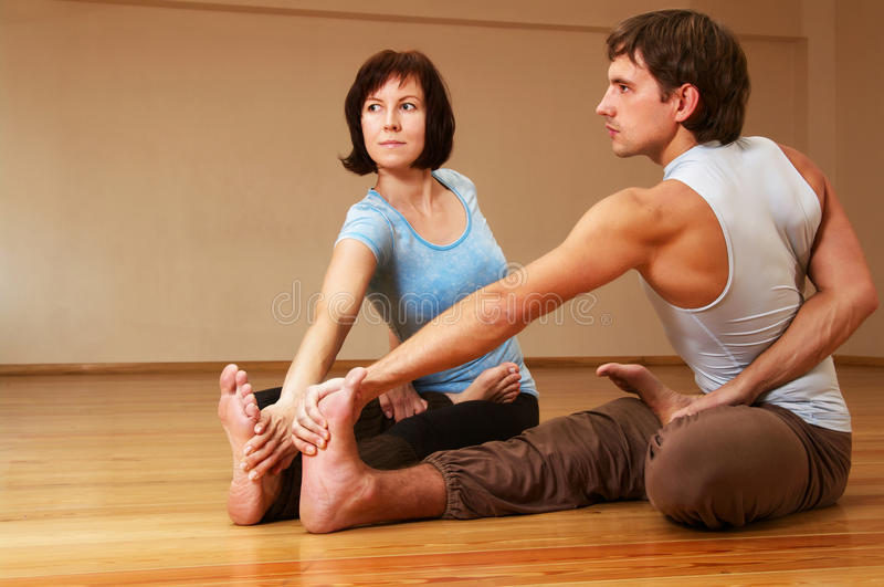Homme et femme faisant le yoga photos stock