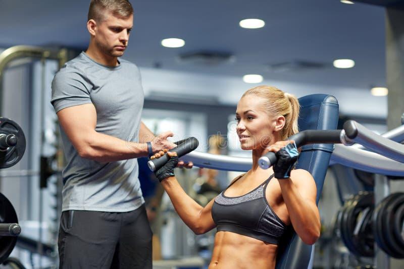 Homme et femme fléchissant des muscles sur la machine de gymnase image libre de droits