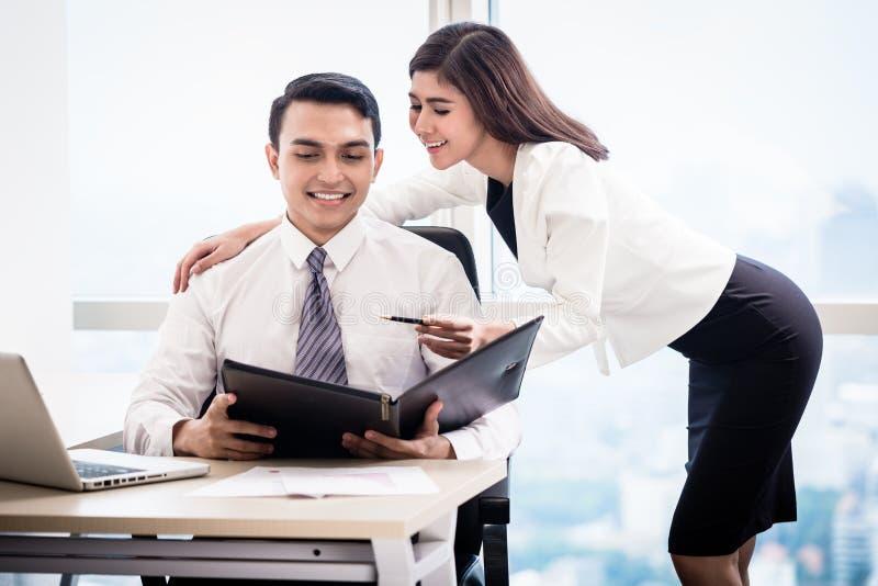 Homme et femme flirtant dans le bureau image stock