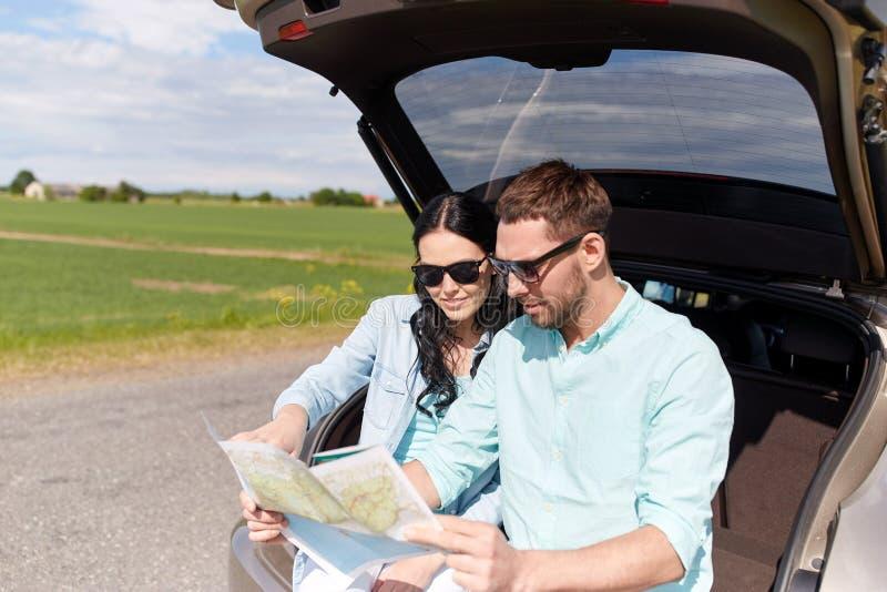 Homme et femme heureux avec la carte de route à la voiture de berline avec hayon arrière photographie stock
