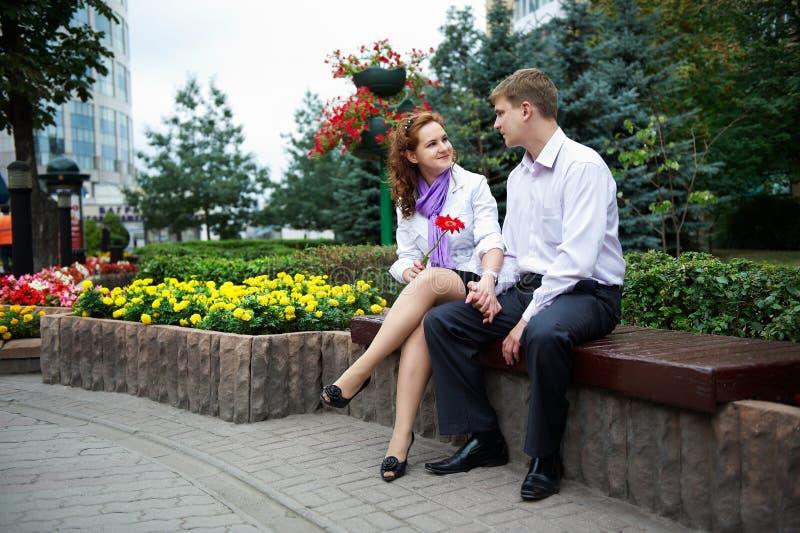 Homme et femme heureux sur le banc en stationnement de fleur photographie stock