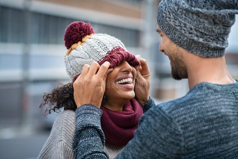 Homme et femme jouant avec le chapeau d'hiver image libre de droits