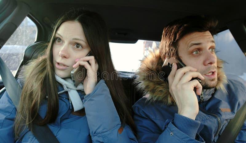 Homme et femme jurant leurs téléphones portables se reposant dans la voiture image stock