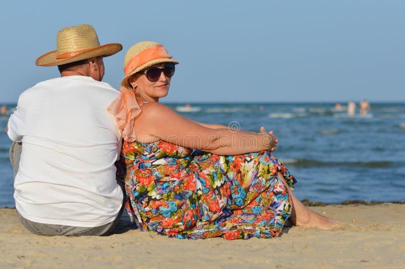 Homme et femme mûrs heureux de couples s'asseyant au bord de la mer sur la plage sablonneuse photo libre de droits