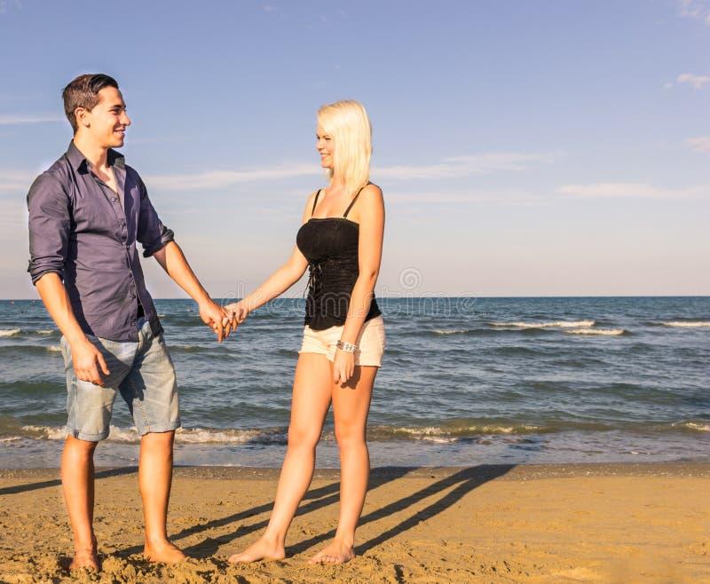 Homme et femme marchant et parlant sur la plage photos libres de droits